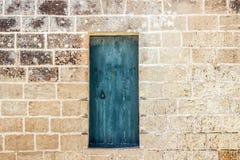 Alte blaue Tür auf Backsteinmauer Stockbilder