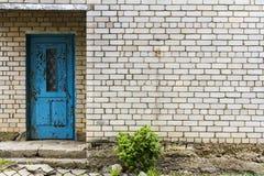 Alte blaue Tür auf einer weißen Backsteinmauer Stockbild