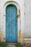 Alte blaue Tür in der rustikalen Retro- Wand Lizenzfreie Stockbilder