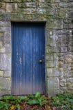 Alte blaue Tür in der Steinwand Stockbilder
