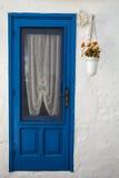 Alte blaue Tür des weißen Hauses Blumentopfhängen Stockfotografie