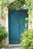 Alte blaue Tür mit Blumen Stockbilder