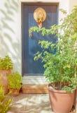Alte blaue Tür mit Hut und Blumen Stockbild