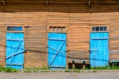 Alte blaue Türen auf hölzerner Fassade Stockfoto