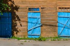 Alte blaue Türen auf hölzerner Fassade Lizenzfreie Stockfotografie