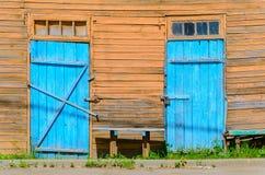 Alte blaue Türen auf hölzerner Fassade Lizenzfreie Stockbilder