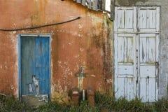 Alte blaue und weiße Holztüren eines verlassenen orange Hauses Stockfotografie