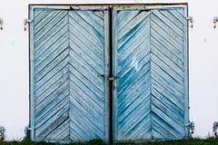alte, blaue, verdrehte Garagentoren auf einer Einsturzbacksteinmauer Stockbilder