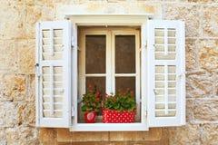 Alte Blendenverschlußfenster mit Blumen. Montenegro. Lizenzfreies Stockfoto