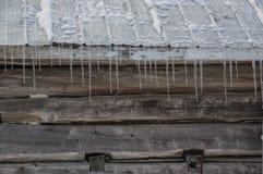 Alte Blockhausscheune Snowy mit Eiszapfenhintergrund Lizenzfreie Stockbilder