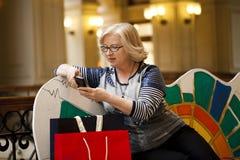 Alte Blondine, die telefonisch mit Einkaufstaschen nennen Lizenzfreie Stockfotos