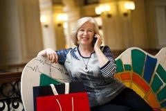 Alte Blondine, die telefonisch mit Einkaufstaschen nennen Lizenzfreie Stockfotografie