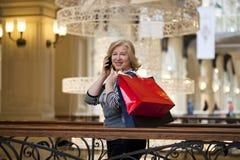 Alte Blondine, die telefonisch mit Einkaufstaschen nennen Lizenzfreies Stockfoto