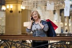 Alte Blondine, die telefonisch mit Einkaufstaschen nennen Stockfotos