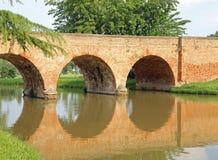 alte Bogenbrücke hergestellt von den roten Backsteinen mit dem Fluss Stockbilder