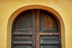 Alte Bogenholztür auf gelber Wand Lizenzfreies Stockbild