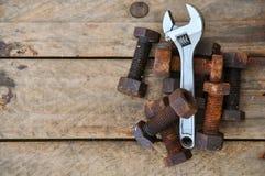 Alte Bolzen mit Werkzeugen des justierbaren Schlüssels auf hölzernem Hintergrund Stockbild