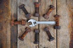 Alte Bolzen mit Werkzeugen des justierbaren Schlüssels auf hölzernem Hintergrund Stockfotografie