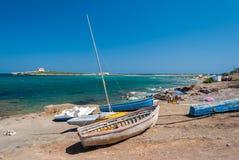 Alte Boote in der Küstenlinie von Portopalo (Süd-Sizilien) Lizenzfreie Stockbilder