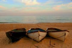 Alte Boote, die auf einem sandigen Strand bei Sonnenuntergang stillstehen Lizenzfreies Stockfoto