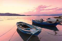 Alte Boote im Hafen Bunter Sonnenaufgang oder Sonnenuntergang, Wolken und Berge Stockfotos
