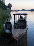 Alte Boote nähern sich Bank im Fluss vor Sonnenuntergang Stockfotografie