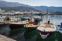 Alte Boote am Pier auf dem Hintergrund von Bergen und von Yachten lizenzfreie stockfotos