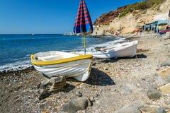 Alte Boote und Regenschirm auf dem Strand von Santorini-Insel Stockfotos