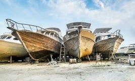 Alte Boote werden auf dem Ufer am Hafen repariert Lizenzfreie Stockfotografie