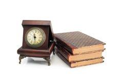 Alte Borduhr und Bücher Stockbilder