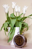 Alte Borduhr und Tulpen Stockbilder