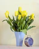 Alte Borduhr und Tulpen Stockfotos