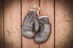Alte Boxhandschuhe auf hölzerner Wand Lizenzfreies Stockfoto