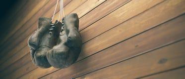 Alte Boxhandschuhe hängen am Nagel auf hölzerner Wand mit Kopienraum für Text Hohe Auflösung 3D übertragen stockbilder