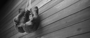 Alte Boxhandschuhe hängen am Nagel auf hölzerner Wand mit Kopienraum für Text Hohe Auflösung 3D übertragen stockbild