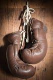 Alte Boxhandschuhe, hängend an der hölzernen Wand Lizenzfreie Stockfotografie