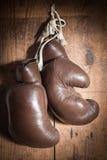 Alte Boxhandschuhe, hängend an der hölzernen Wand Stockfotografie