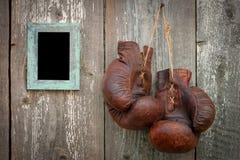 Alte Boxhandschuhe und Rahmen für Foto Lizenzfreies Stockfoto