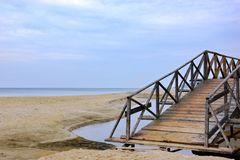 Alte Brücke über kleinem Fluss an der Seeküste Lizenzfreie Stockfotos