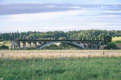 alte Brücke mit Weizen-Feld und elektrische Pfosten mit Drähten - vint Lizenzfreie Stockfotografie