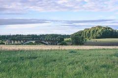 alte Brücke mit Weizen-Feld und elektrische Pfosten mit Drähten - vint Lizenzfreie Stockbilder