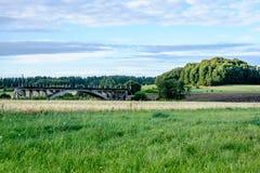 alte Brücke mit Weizen-Feld und elektrische Pfosten mit Drähten Stockfotografie