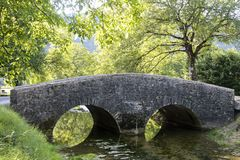 Alte Brücke nahe mittelalterlichem Dorf von Baume les Messieurs in Frankreich Stockbild