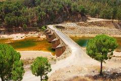 Alte Brücke und roter Fluss, saure Wasserhaltung. Lizenzfreies Stockfoto