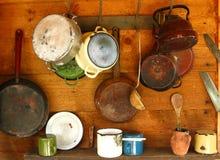 Alte Bratpfannen und kochen Töpfe, die an einer hölzernen Wand hängen Stockbild