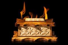 Alte braune hölzerne Schatulle in der Feuerflamme auf schwarzem Hintergrund Lizenzfreie Stockbilder