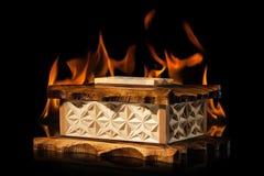 Alte braune hölzerne Schatulle in der Feuerflamme auf schwarzem Hintergrund Lizenzfreies Stockfoto
