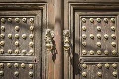 Alte braune Holztür mit goldenen metallischen Verzierungen Lizenzfreies Stockfoto