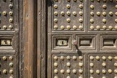 Alte braune Holztür mit goldenen metallischen Verzierungen Lizenzfreie Stockfotografie