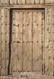 Alte braune Holztür mit metallischen Verzierungen auf einer hölzernen Wand Lizenzfreie Stockbilder